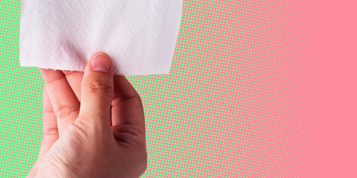 Hand getting toilet paper on pink and green background