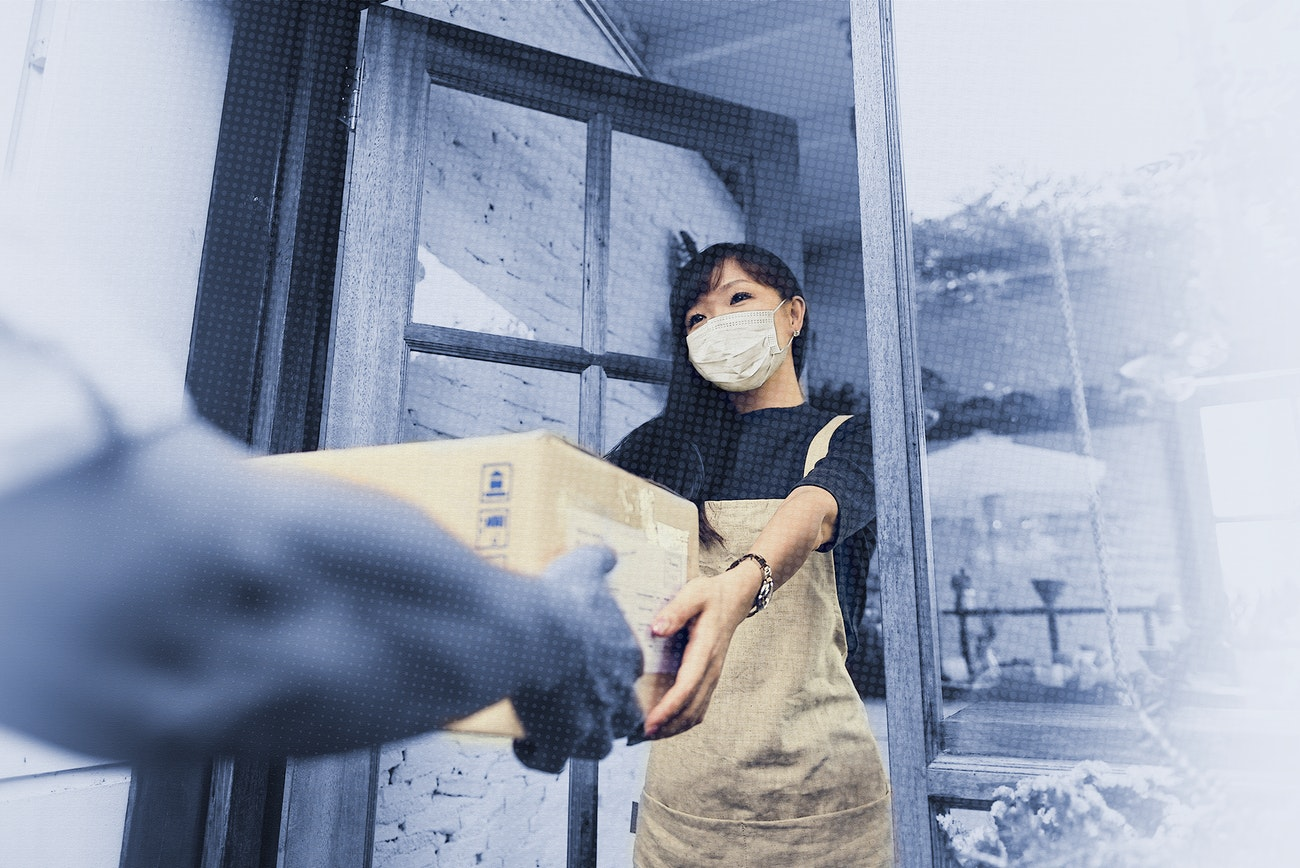 Woman in a face mask receiving a delivery box