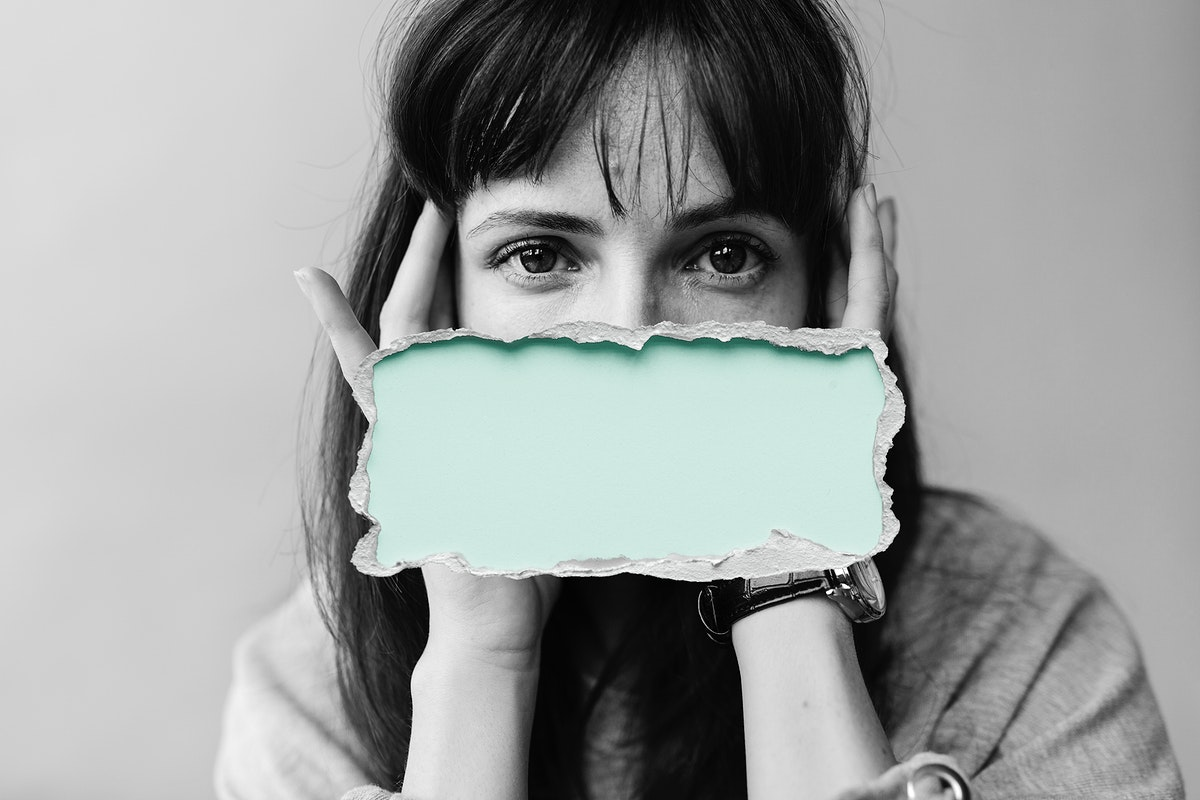 Woman with a green box over her mouth