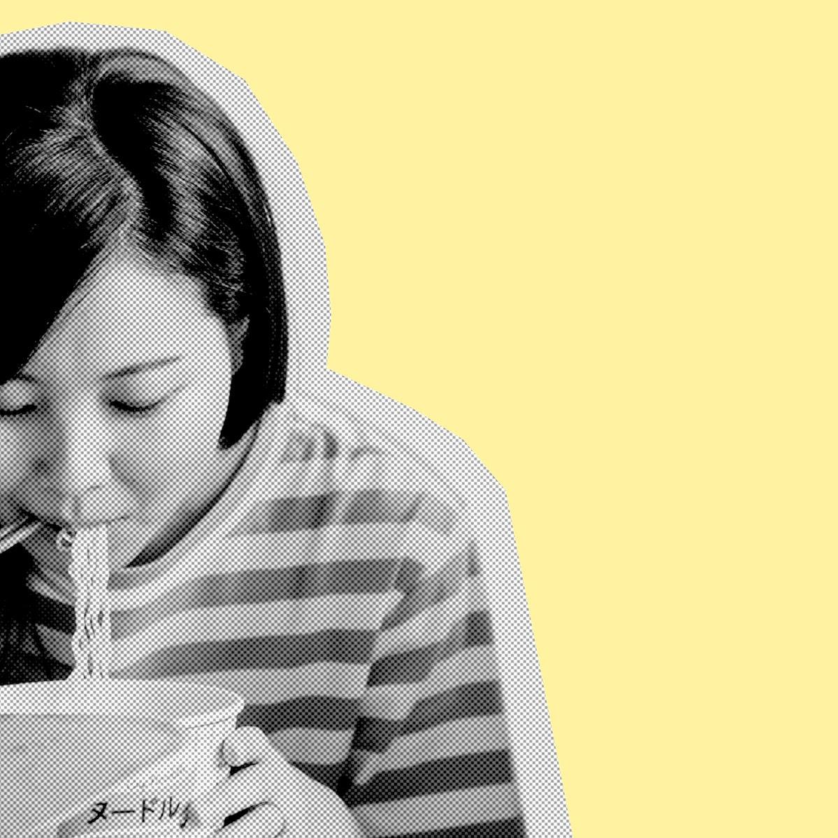 Asian woman eating instant noodles during coronavirus quarantine