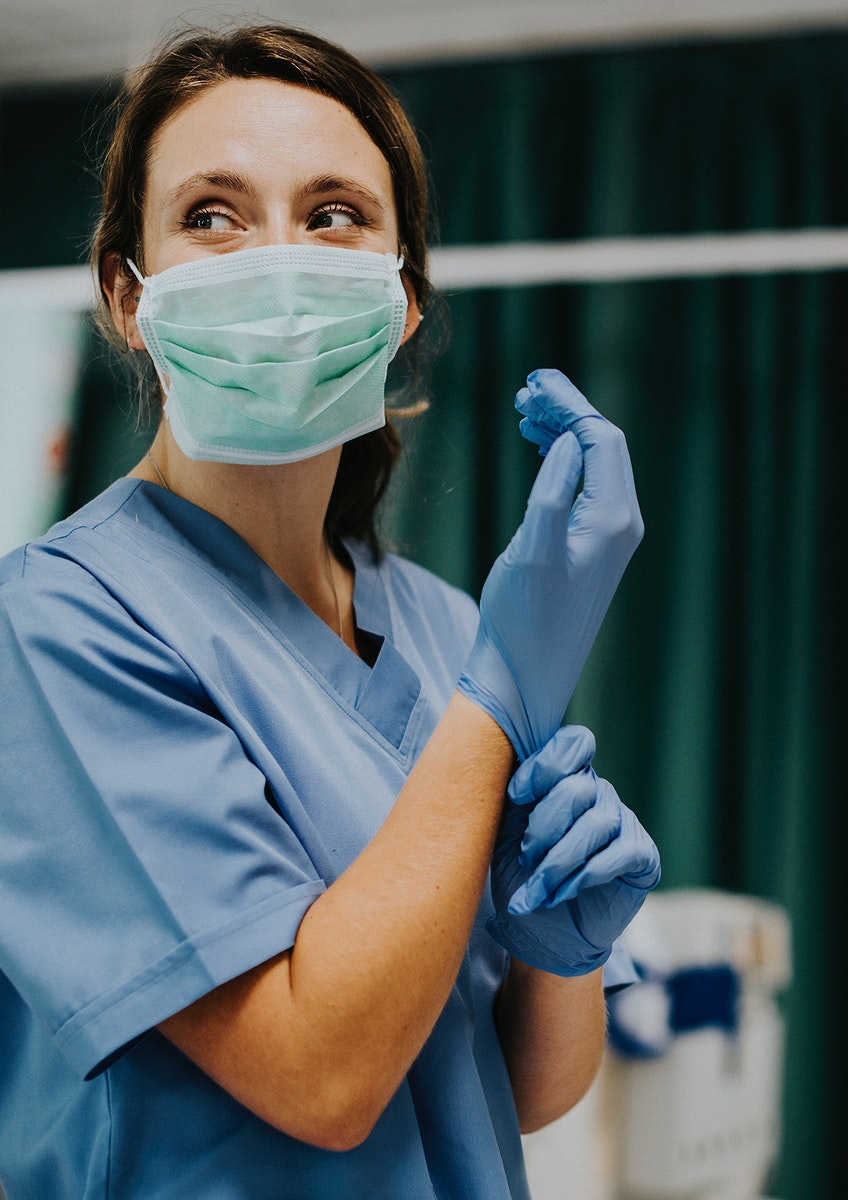 Female nurse with a mask putting on gloves