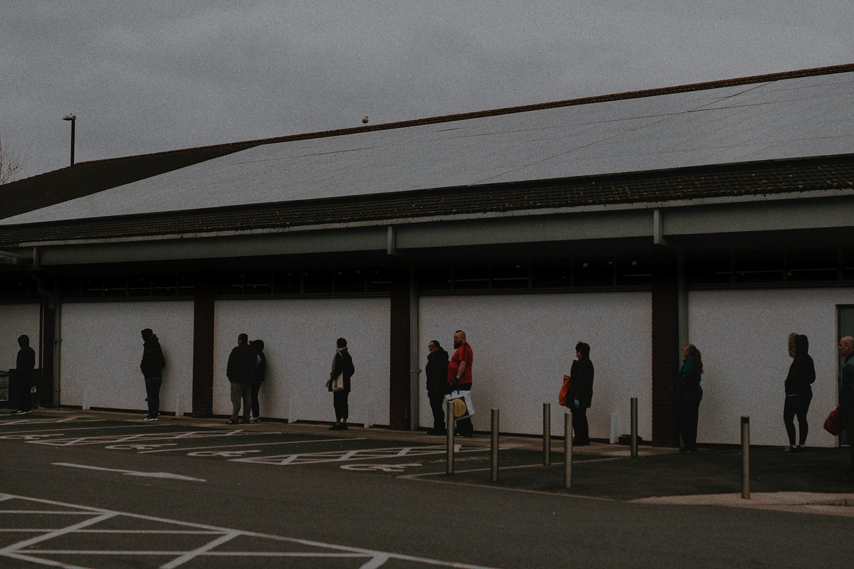 People lining up outside the supermarket social distancing during coronavirus pandemic. MARCH 30, 2020 - BRISTOL, UK