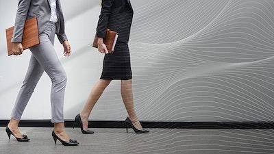 5e101d06db81 Two businesswomen walking in a corridor