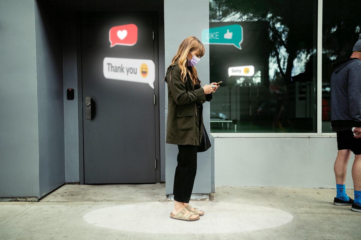 Woman texting psd social distancing in a queue