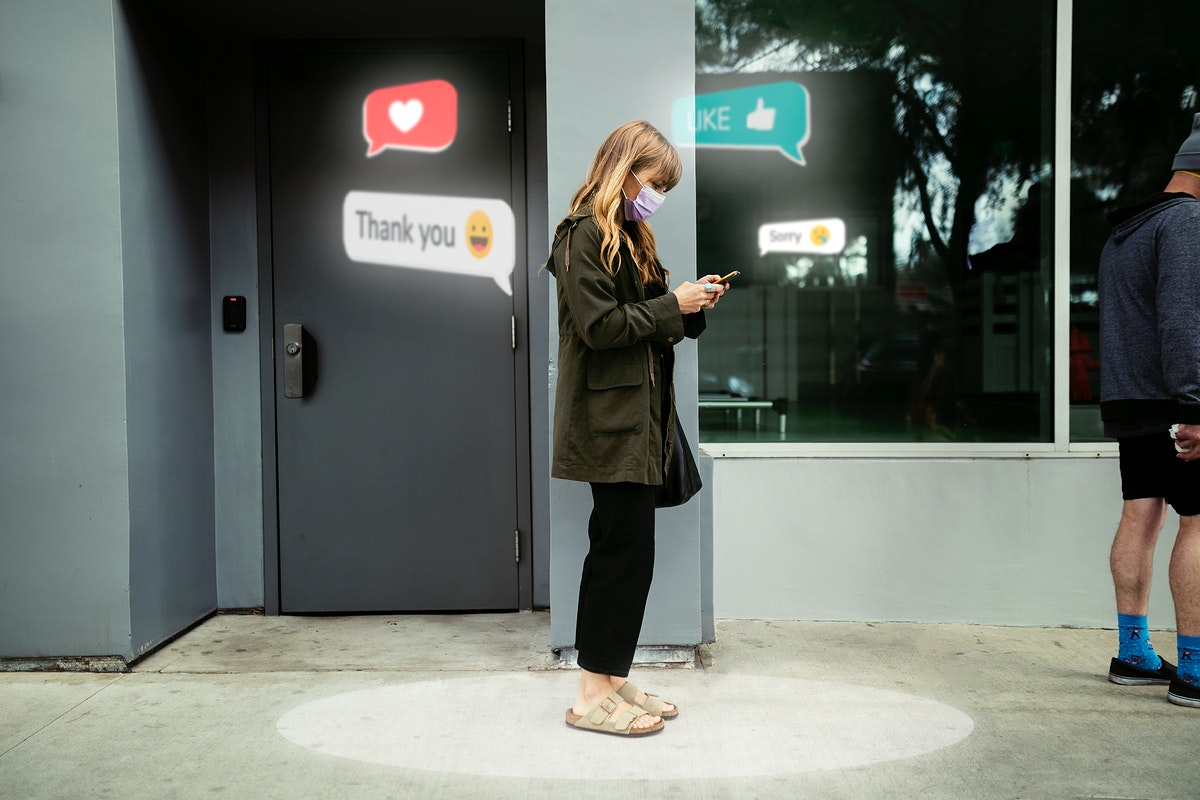 Woman texting while social distancing in a queue