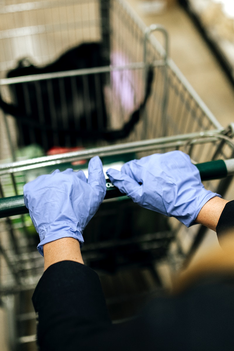 Woman in a face mask wearing latex gloves while shopping in a supermarket during coronavirus quarantine