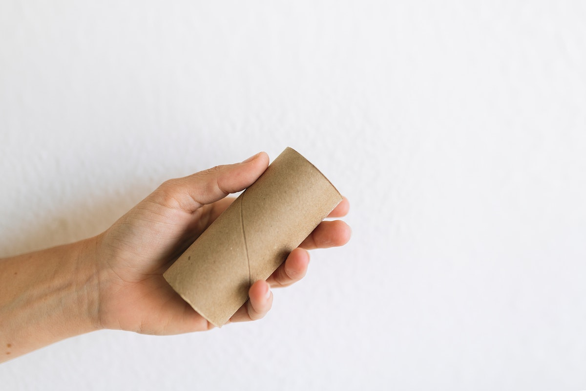 Hand with an empty tissue paper roll on a white background