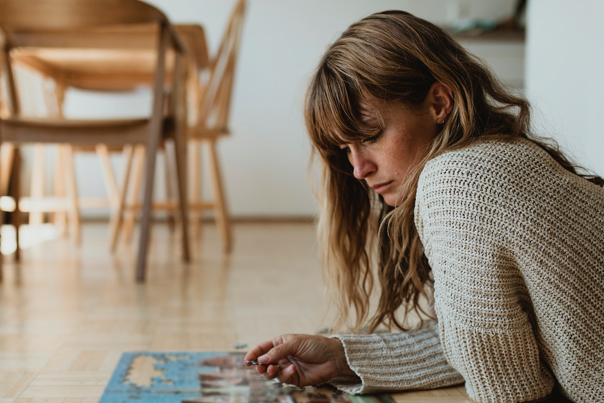 Woman putting together a jigsaw puzzle during self quarantine