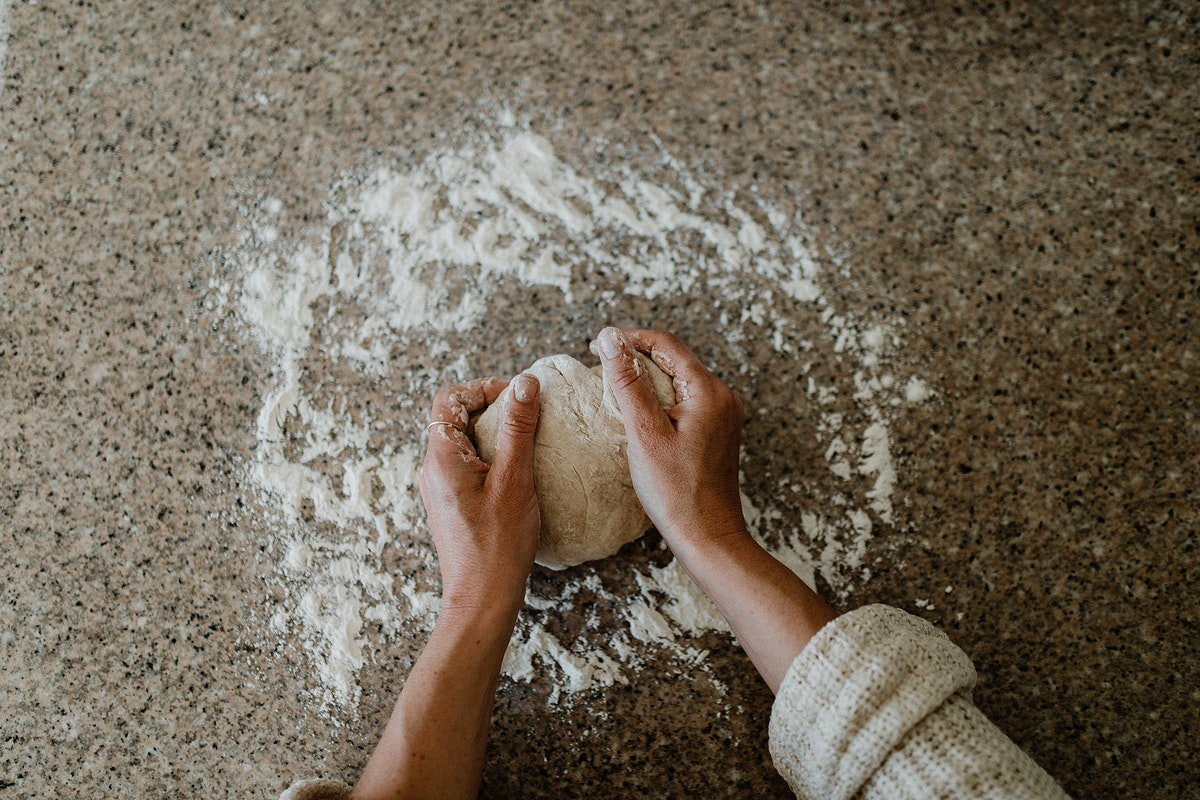 Woman kneading sourdough in her kitchen during quarantine