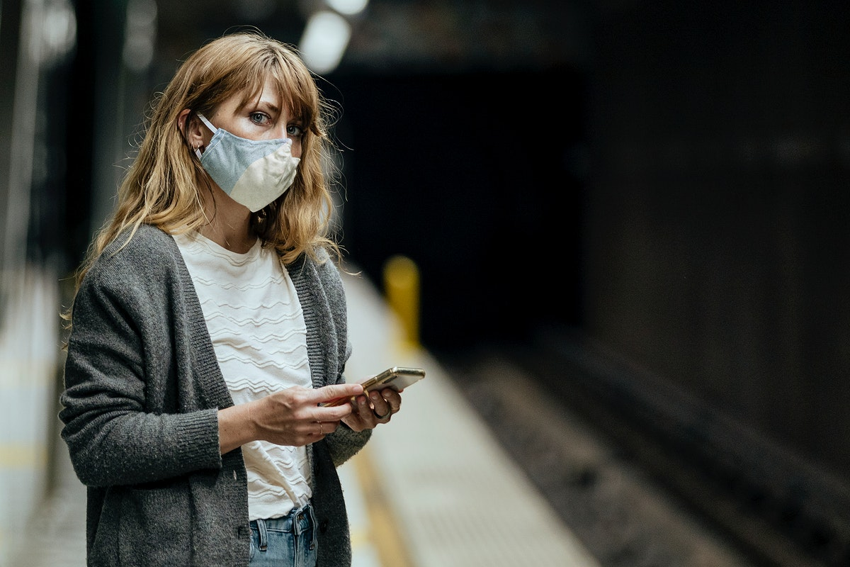 Woman wearing a mask while waiting for the train during the coronavirus pandemic