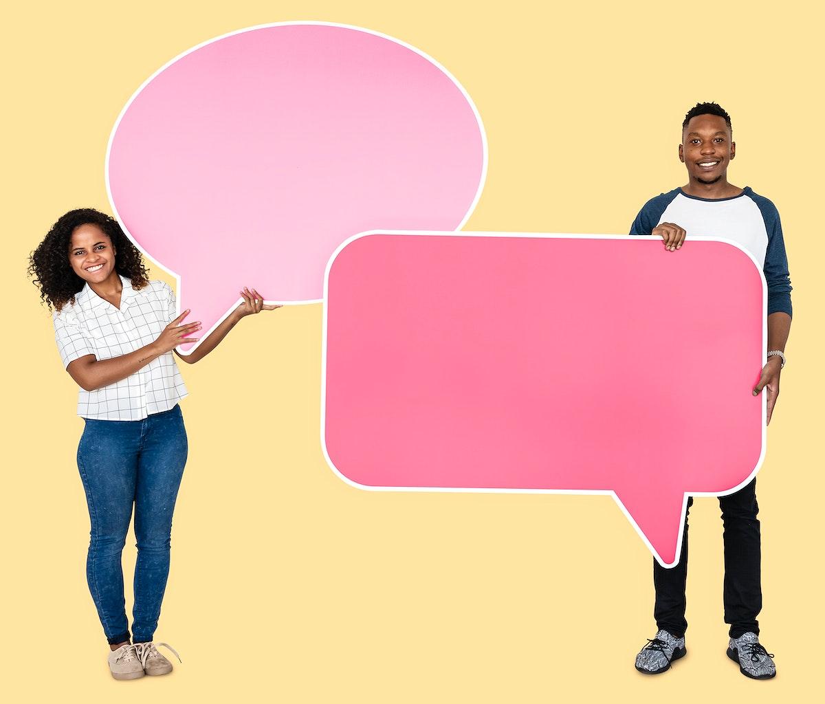 Couple holding empty pink speech bubbles