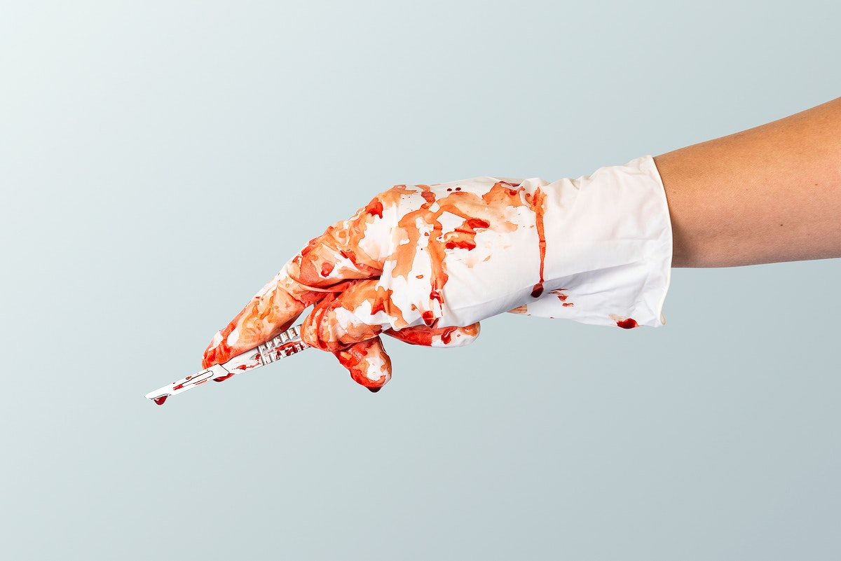 Doctor bloody hand in a glove holding a scalpel