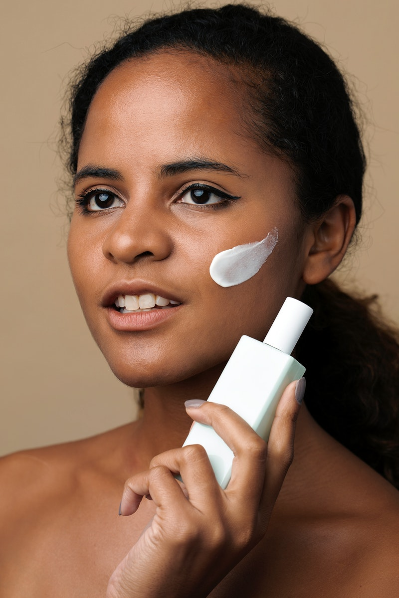 Beautiful African American woman holding a facial cream container