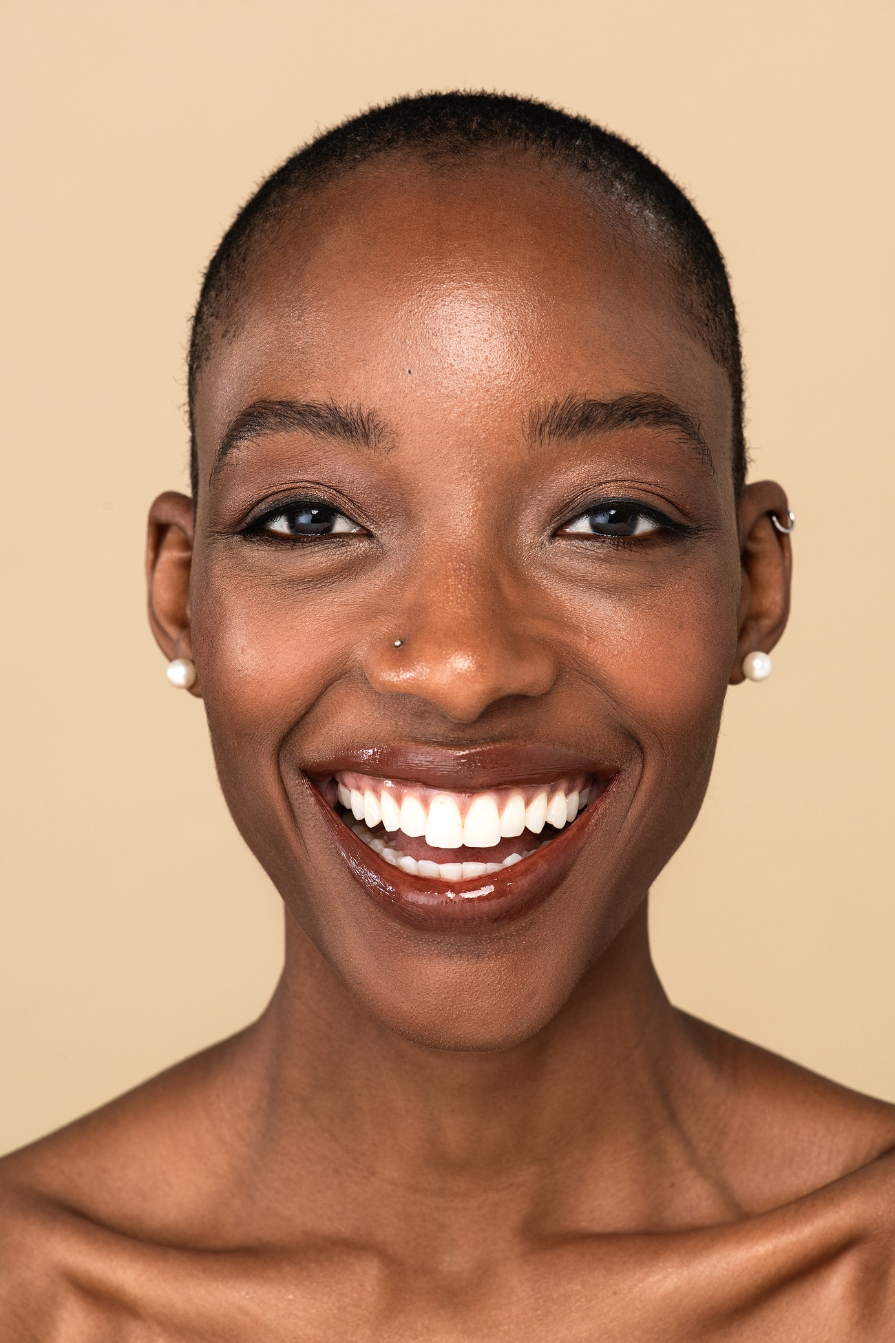 Happy nude black woman against a beige background