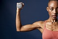 Active black woman lifting a dumbbell on blue background