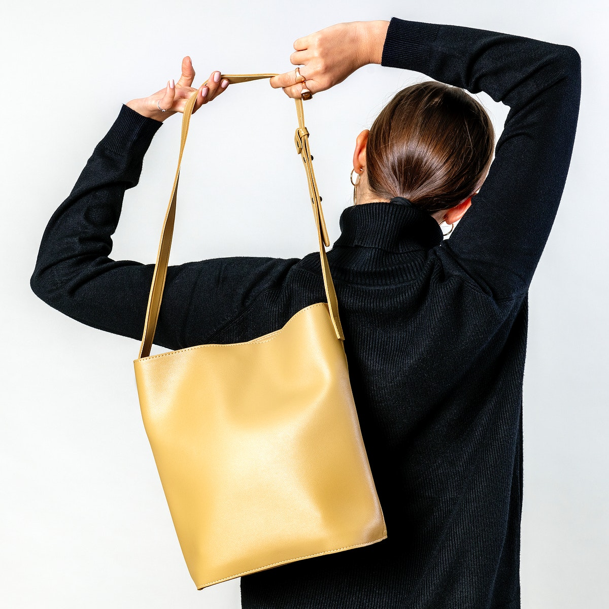 Woman from behind with a yellow cross body bag