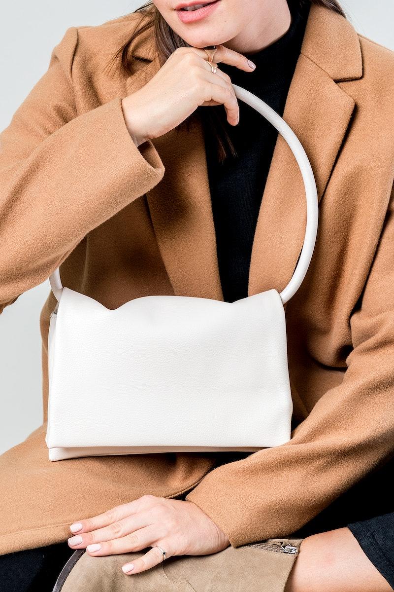 Woman with a while kangaroo print hand bag mockup
