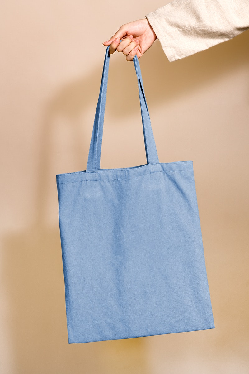 Woman holding a blue tote bag in her hand
