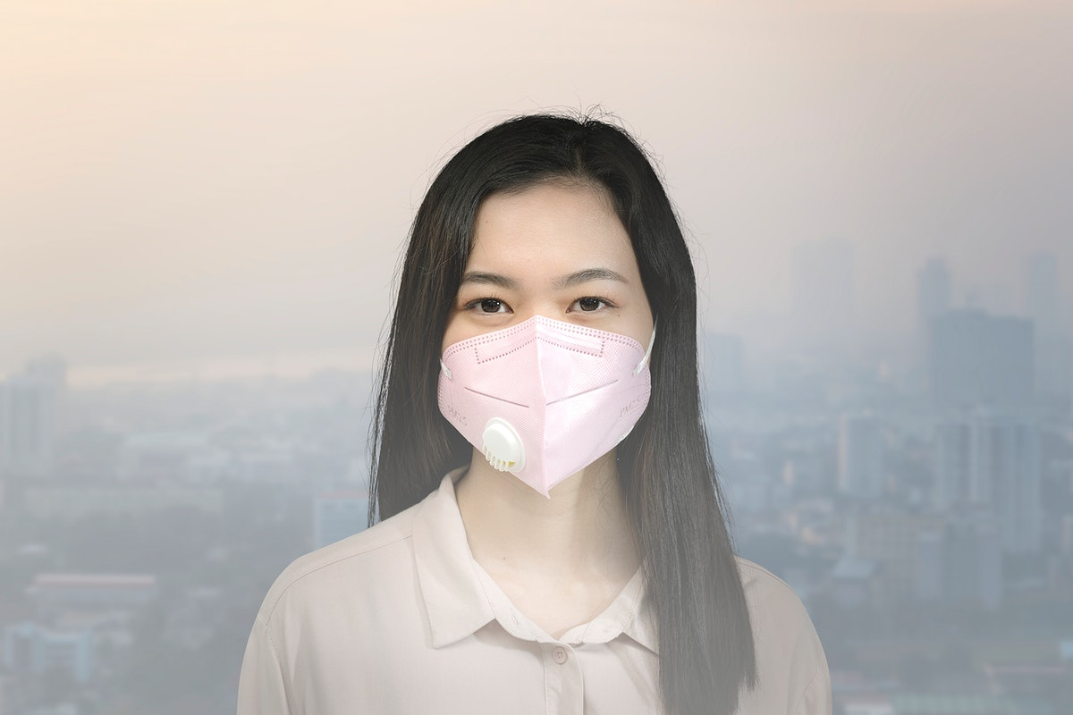Asian woman wearing a mask in a polluted city