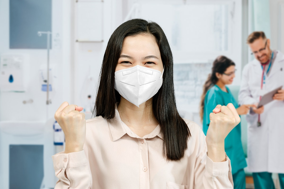 Asian woman wearing a mask raising her hands up in a hospital