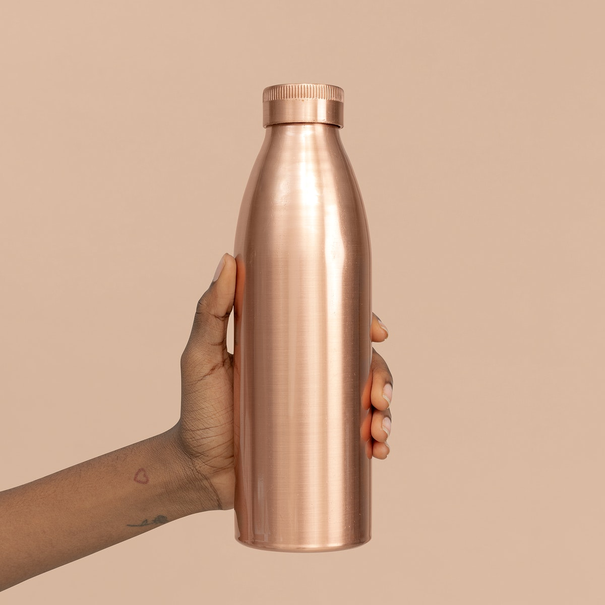 Hand holding a copper stainless steel bottle mockup