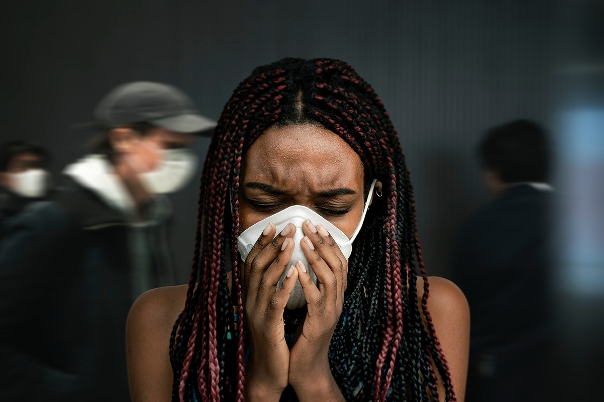 Black woman wearing a mask and coughing in a crowded