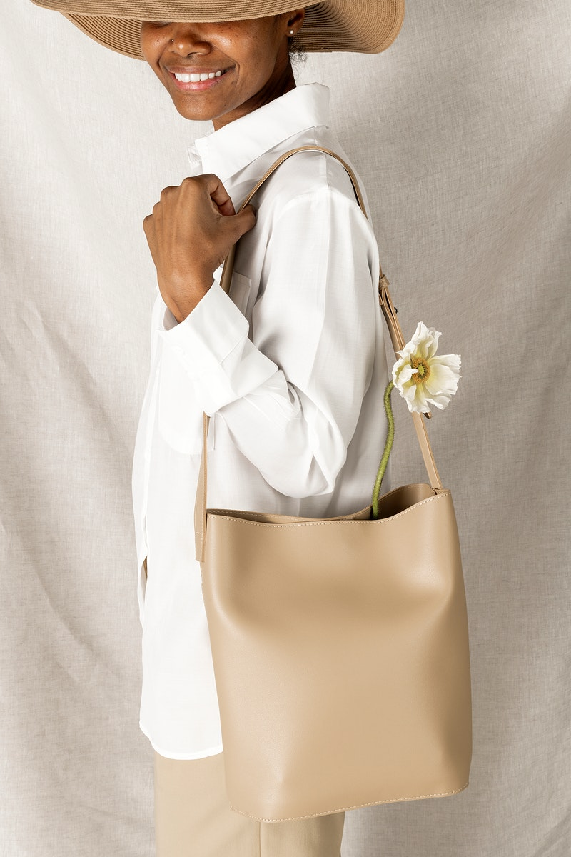 Happy black woman with a white poppy flower in her cream bucket bag