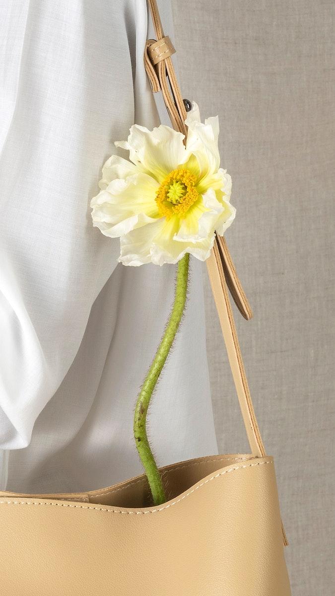 White poppy flower in a beige bag