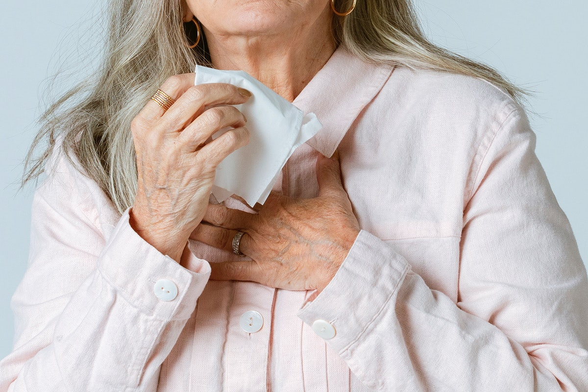 Coronavirus infected senior woman blowing nose into a tissue paper
