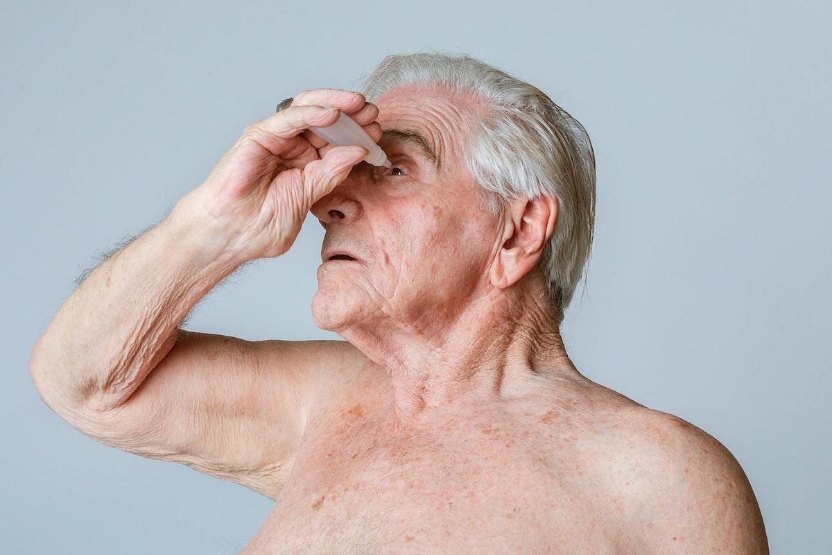 Senior man applying eye drops