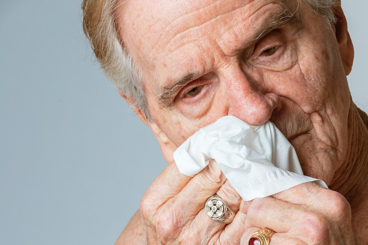 Coronavirus infected senior rman blowing nose into a tissue paper