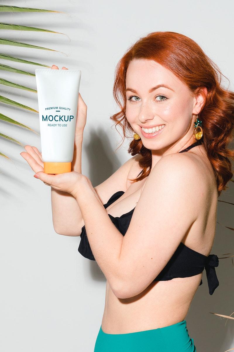 Sexy woman in a bikini holding a sunscreen tube mockup