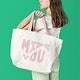 Beige tote bag mockup psd with pink MISS YOU typography